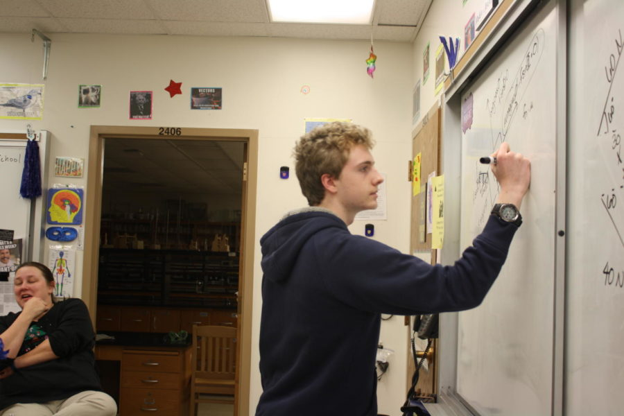 Junior+David+Walker+writes+an+equation+on+the+board.+%E2%80%9CIt%E2%80%99s+definitely+teacher+led%2C%22+Walker+said.+%22Students+in+that+class+%28Engineering%29%2C+we%E2%80%99ll+do+our+own+projects+and+things%2C+but+it%E2%80%99s+not+any+sort+of+an+open+form+type+of+class.+They%E2%80%99ll+tell+you+what+to+do%2C+you+just+have+your+own+way+of+doing+it.%E2%80%9D+Walker+is+in+his+second+year+of+engineering+at+WHS.