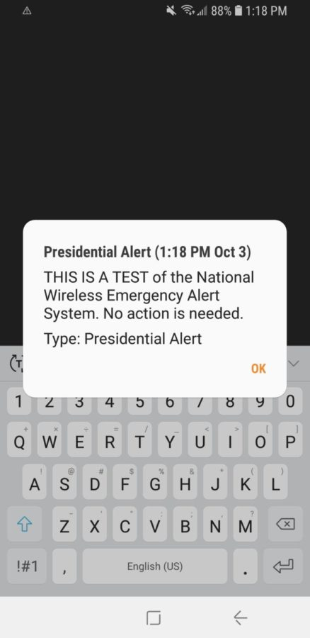 The Presidential Alert appears across the screen of a WHS teacher's cell phone screen.
