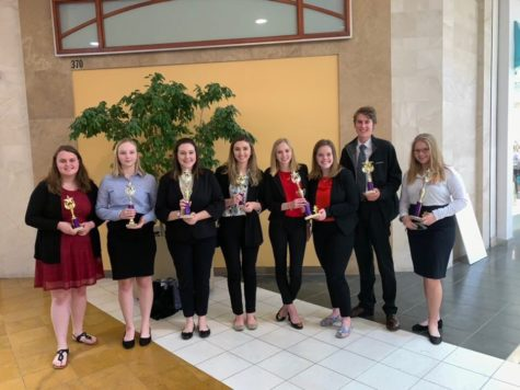 "WHS DECA students pose with their awards at the district competition Feb. 6. ""It's really cool to be able to go [to state] and see everybody you're competing against and all the organizations that they helped,"" senior Sophie Hellebusch said. Hellebusch plans to attend the University of Nebraska next year as a business major."