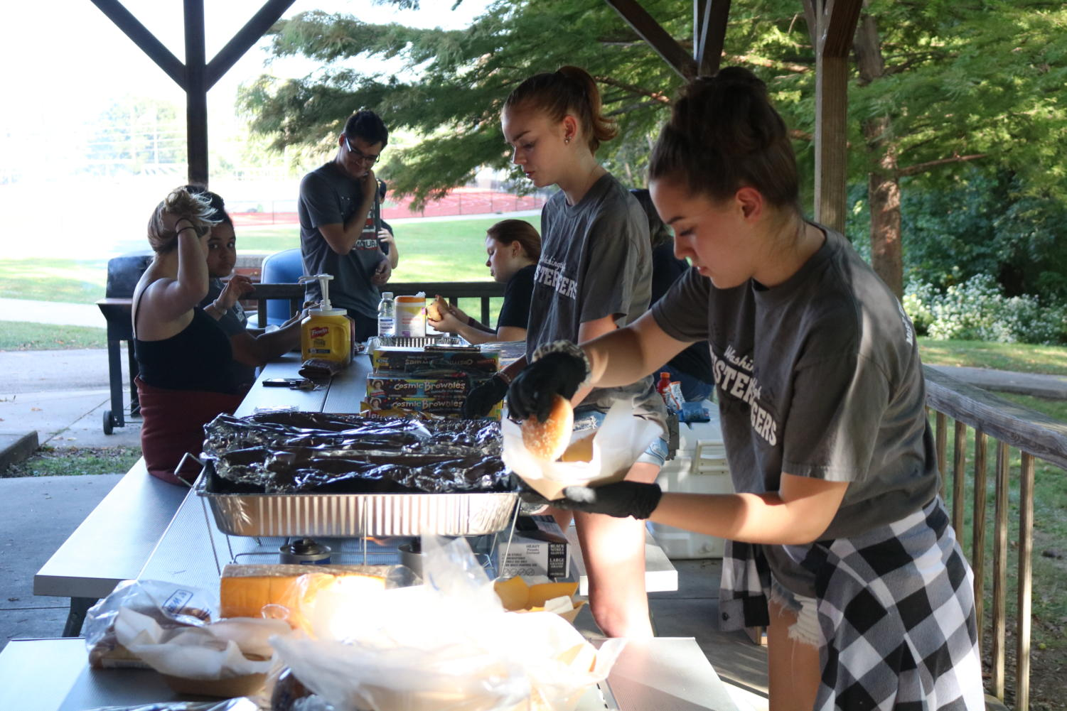 """Students get food and enjoy the tailgate before the Homecoming game against Liberty Sept. 27. """"I think people should come to the tailgates because it's just fun overall, it's just something to do,"""" senior Matthew Amlong said. """"And sometimes we'll have food there, and who doesn't wanna get some grilled hot dogs?"""" The WHS student section have been doing tailgates since the first away football game."""