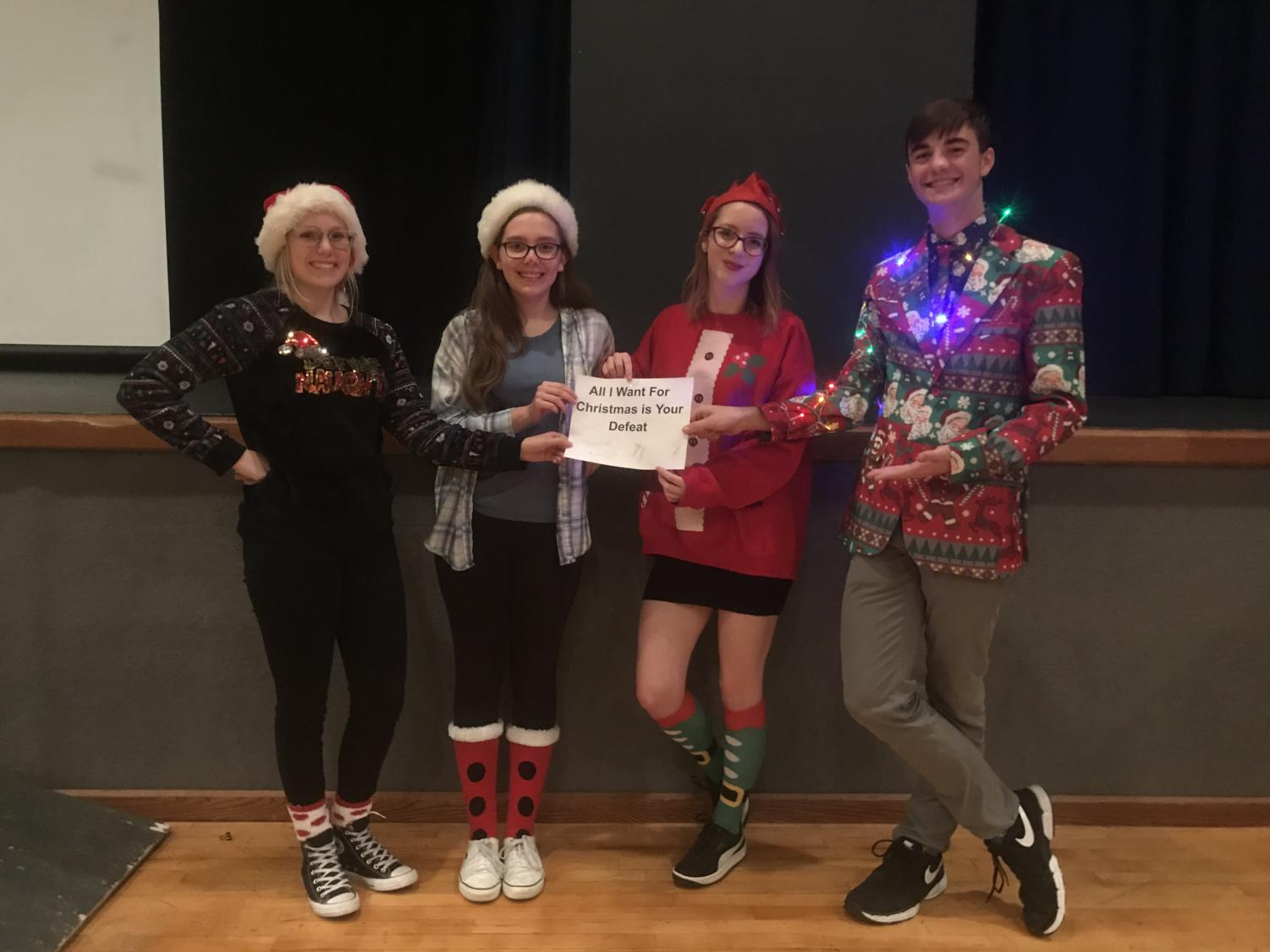 "Pictured above are members of the winning team, ""All I Want for Christmas is Your Defeat."" From left, are senior Sebastian Secor, sophomore Samantha Doepker, senior Audrey Bush and senior Ian Maloney. ""Every year I get so excited because it's the one time I get to show off my catalogue of semi-useless facts,"" Bush said. ""Doing it in front of the whole school is both awesome and nerve-wracking."" Along with placing first against students, the team also defeated an all teacher team."