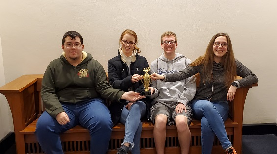 """A WHS scholar bowl team poses with their fourth place trophy at Washington University on Feb. 15. """"Mr. Dennis puts it like this: 'Pick a subject, learn it, know it, hit the button,'"""" sophomore Silas Clements said. This same day, senior Audrey Bush was awarded with a 10th place scoring medal from the preliminary bracket."""