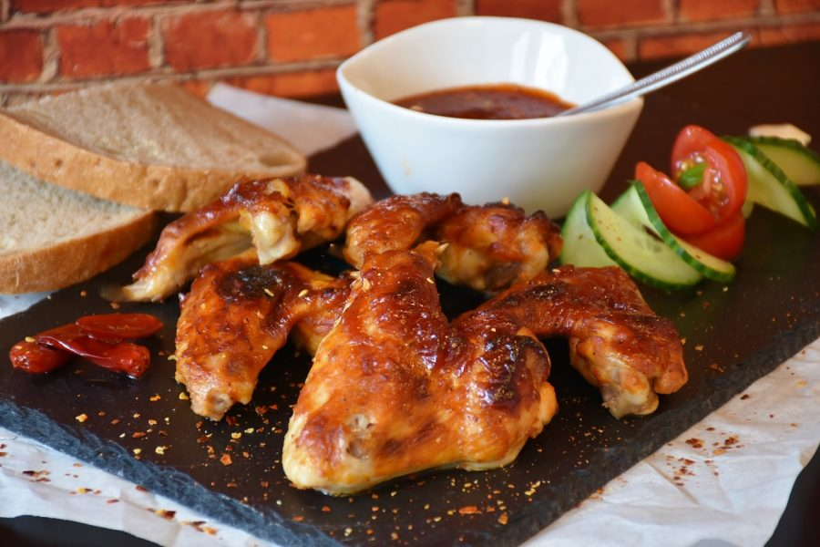 A neatly prepared plate of chicken wings served with vegetables, bread and dipping sauce.