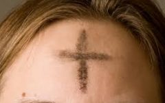 A girl gets marked on her forehead with the cross for Ash Wednesday.